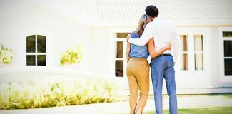 Rear view of couple standing with arm around royalty free stock photo