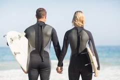 Rear view of couple with surfboard holding hand on the beach Stock Photos