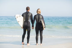 Rear view of couple with surfboard holding hand on the beach Royalty Free Stock Photos