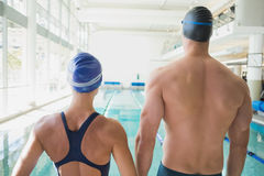 Rear view of couple swimmers by pool at leisure center. Rear view of a fit male and female swimmers by the pool at leisure center Stock Photography