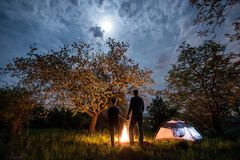 Rear view of couple tourists standing at a campfire, holding hands near tent under trees and night sky with the moon Stock Images
