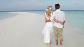 Rear View Of Couple Walking Along Beach At Wedding Royalty Free Stock Photo