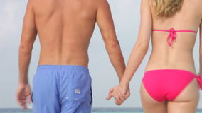 Rear View Of Couple Walking On Beautiful Tropical Beach stock video footage