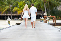 Rear View Of Couple Walking On Wooden Jetty Stock Photography