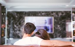 Rear view of couple watching television in living room. stock photo