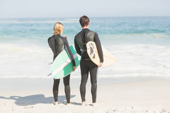 Rear view of couple in wetsuit with surfboard standing on the beach Royalty Free Stock Photos