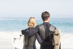Rear view of couple in wetsuit with surfboard standing on the beach Stock Photo