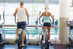 Rear view of couple working on x-trainers at gym Royalty Free Stock Image