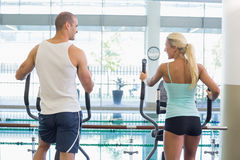 Rear view of couple working on x-trainers at gym Royalty Free Stock Images