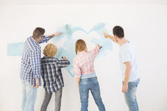 Rear view of couples painting wall in new home Stock Photos