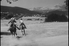 Rear view of cowboys on horses galloping through prairie land stock video footage