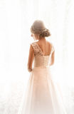Rear view of cute blonde bride posing at window at morning Royalty Free Stock Photo