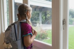 Cute girl with school bag looking outside through window in a comfortable home. Rear view of cute Caucasian girl with school bag looking at camera in a royalty free stock images