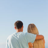 Rear view of cute couple admiring blue sky Royalty Free Stock Photography