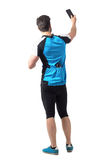 Rear view of cyclist in jersey shirt with water bottle in back pockets taking picture with smart phone Stock Images