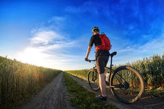 Rear view of the cyclist riding mountain bike on the trail against beautiful sky. Stock Photo