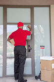 Rear view of a delivery man knocking on door Royalty Free Stock Images