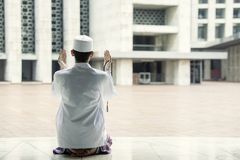 Devout man prays to the Allah in the mosque. Rear view of a devout man praying to the Allah while sitting in the mosque royalty free stock photography