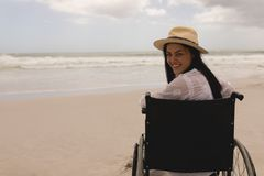 Young woman with hat sitting on wheelchair and looking at camera