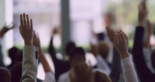 Business professionals raising their hands in a business seminar 4k. Rear view of diverse business professionals raising their hands in a business seminar stock footage