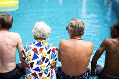 Rear view of diverse senior adults sitting by the pool enjoying stock photo
