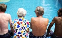 Rear view of diverse senior adults sitting by the pool enjoying summer together stock photography