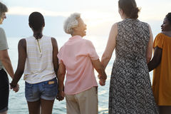 Rear view of diverse senior women holding hands together at the. Beach Royalty Free Stock Photos