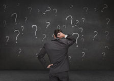 Rear view of a doubtful businessman looking at various question Royalty Free Stock Images