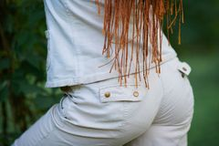 Rear view of dreadlocks fashionable girl dressed in white posing royalty free stock image