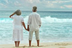 Rear view of elderly couple standing on sandy beach during sunse. T Stock Image