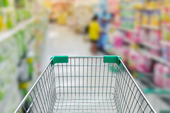 Rear view of empty shopping cart with shopping mall or grocery b. Rear view of empty shopping cart with shopping mall  or grocery background Stock Photo