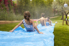 Rear View Of Family Having Fun On Water Slide In Garden Stock Image