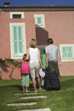 Rear View Of Family With Luggage In Front Of House Stock Image