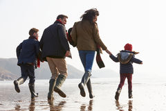 Rear View Of Family Running Along Winter Beach Stock Photo