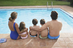 Rear View Of Family Sitting By Pool stock photo