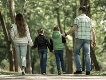 Rear view. family with two children walking hand in hand in the Park. The concept of family entertainment stock photos