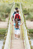 Rear View Of Family Walking Along Wooden Bridge Royalty Free Stock Photography