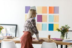 rear view of fashion magazine editor working in modern office with color palette stock photos