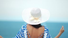 Rear view fashion woman in white hat with naked sexy back admiring sea raising hand. Relaxed travel female enjoying vacation having positive emotion medium stock video