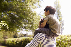 Rear View Of Father Giving Son Ride On Shoulders During Walk Stock Photo