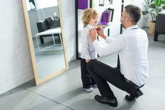Rear view of father helping son tying necktie. At home stock image