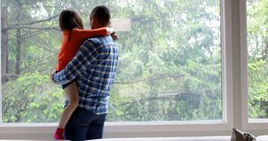 Father holding his daughter while standing near window at home 4k stock video footage
