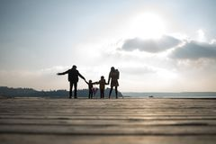 Rear view of father and mother with children holding hands. Standing on wooden pier against evening sky royalty free stock image