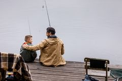 Father and son fishing together. Rear view of father and son fishing together with rods on wooden pier at lake Stock Photos