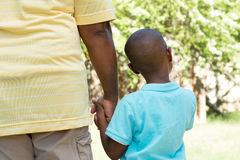 Rear view of father and son holding hands. royalty free stock photography
