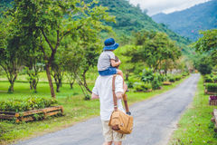 Rear view of father and son walking on a scenic road.  Royalty Free Stock Images