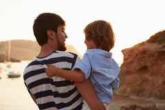Rear View Of Father And Son Watching Sunset Over Harbour Royalty Free Stock Photography