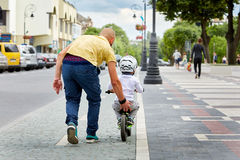 Rear view of father teaching his little son to ride bicycle while protect his in the city park. Young father and little boy dressed in the sportwear and Royalty Free Stock Image