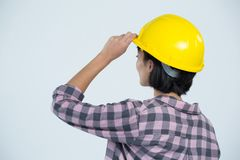 Female architect wearing hard hat against white background Royalty Free Stock Images