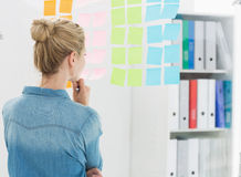 Rear view of a female artist looking at colorful sticky notes Stock Image